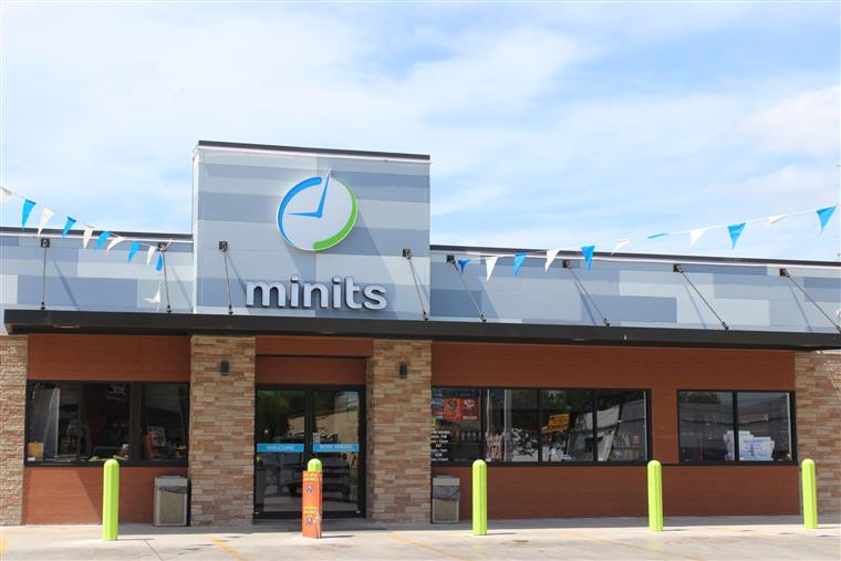 minits location on a sunny day with grand opening flags hanging outside