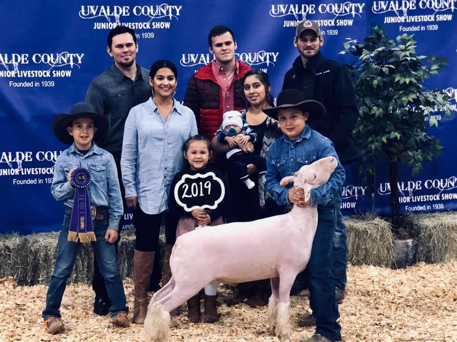 family taking a photo with a goat at the uvalde county junior livestock show founded in 1939