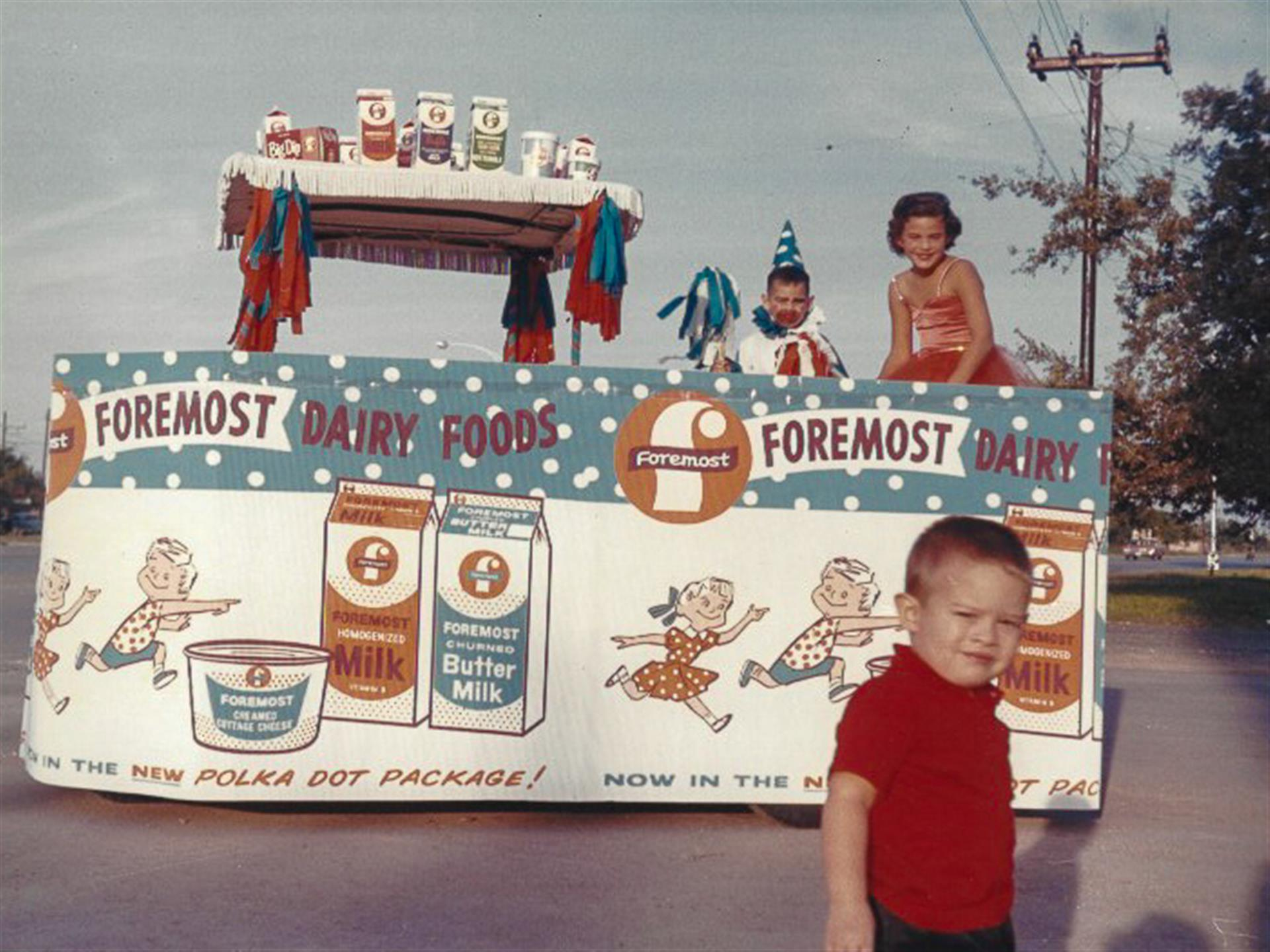 family taking a photo in front of a sign promoting foremost dairy foods