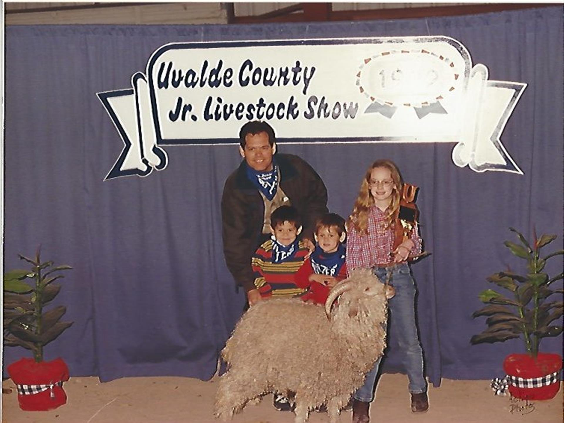 family taking a photo with a goat at the uvalde country jr. livestock show