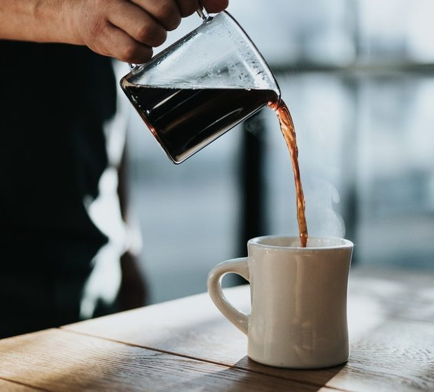 coffee being poured into a mug on a table