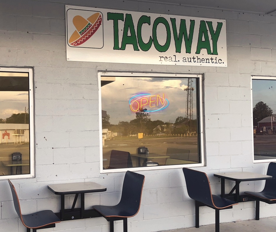 Tables and chairs set up outside Taco Way beside a window