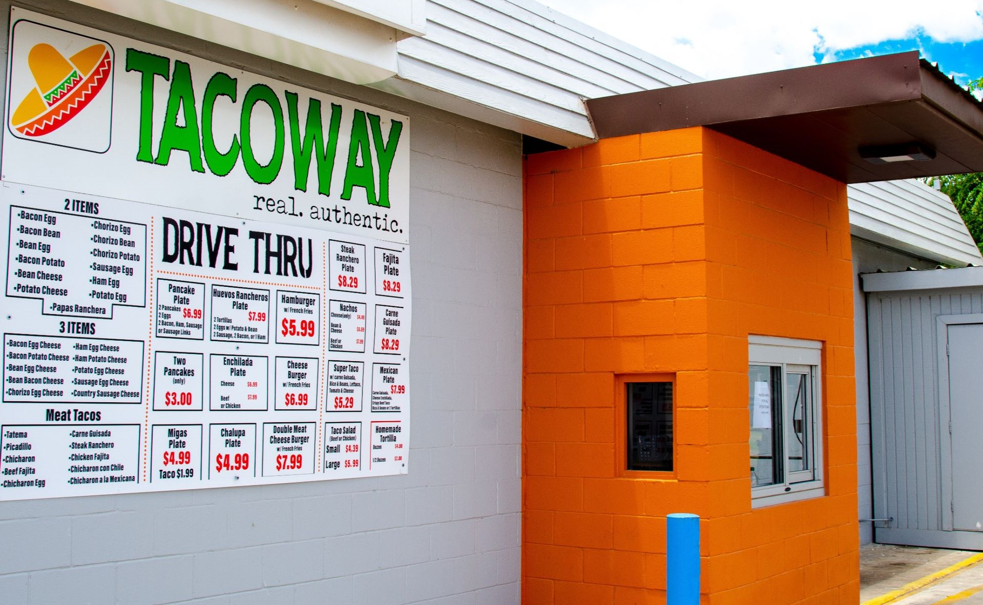 Drive thru window of Taco Way with a large menu on the wall