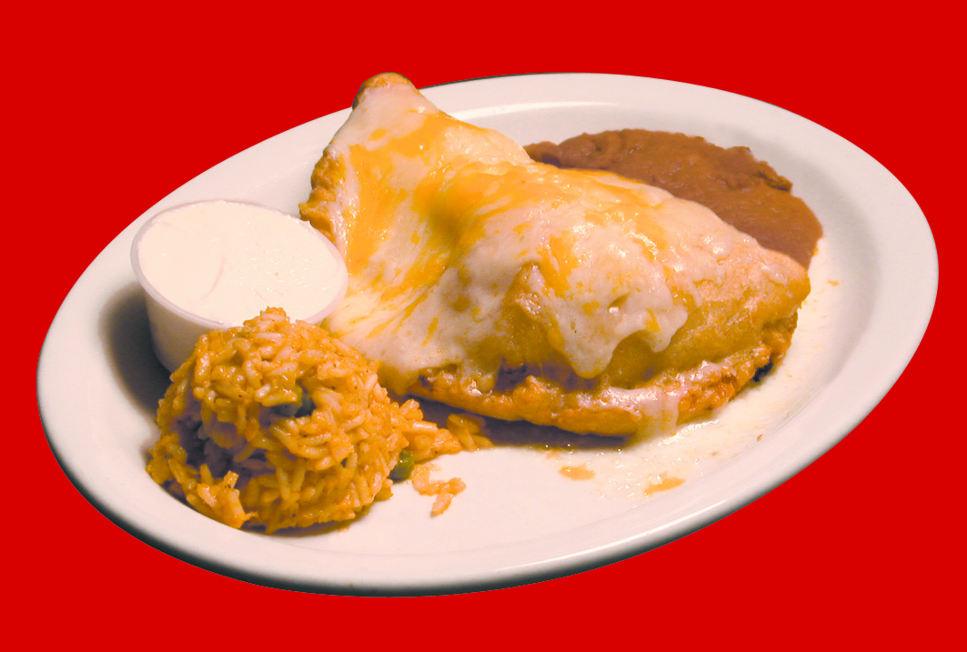 Beef empanada on a plate with rice, beans and sour cream