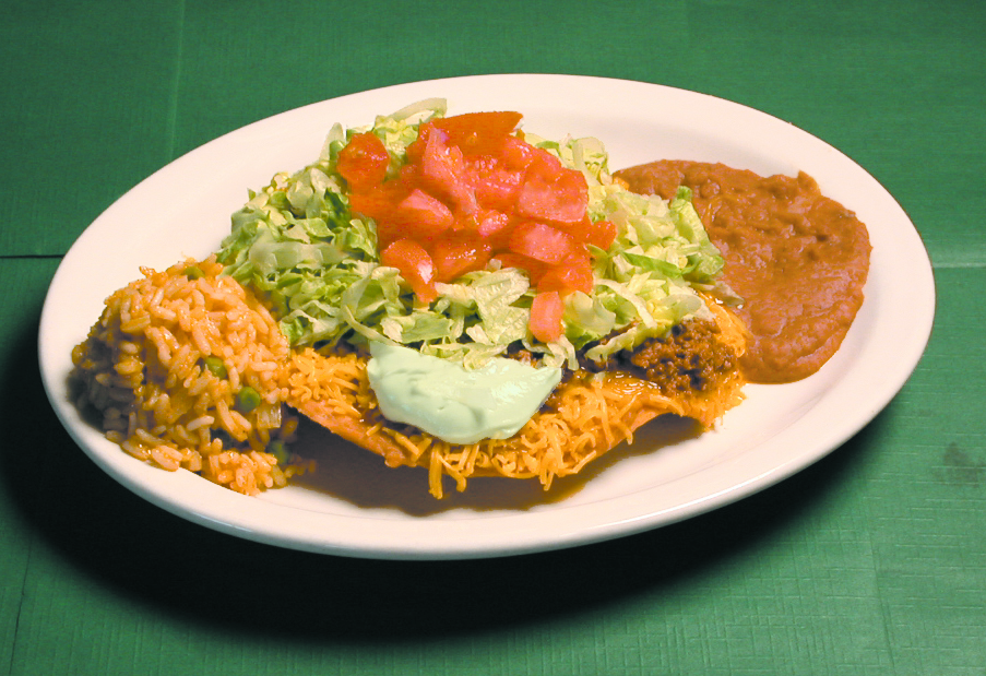 Crispy beef tostada with tomatoes, lettuce and sour cream and a side of rice and beans