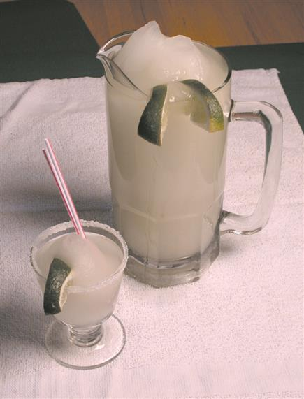 Margarita pitcher and a margarita glass with lime wedges