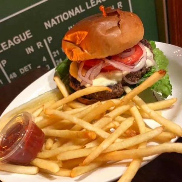 Cheese burger with lettuce and tomato on a plate with French fries and ketchup