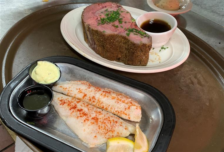 Prime rib on a plate cooked medium rare with a side of au jus. Two broiled filets of walleye, skin on with lemon.