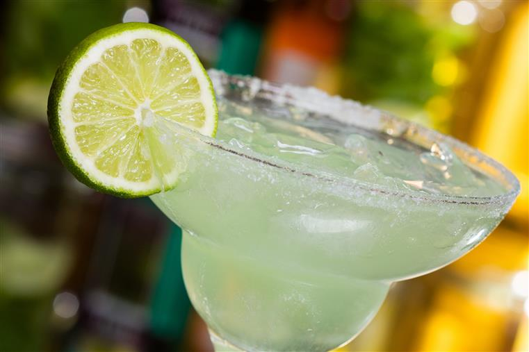 a margarita with a lime wedge