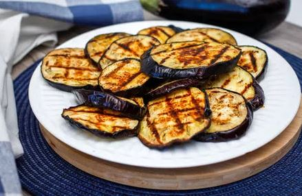 grilled eggplant disks on a plate outside