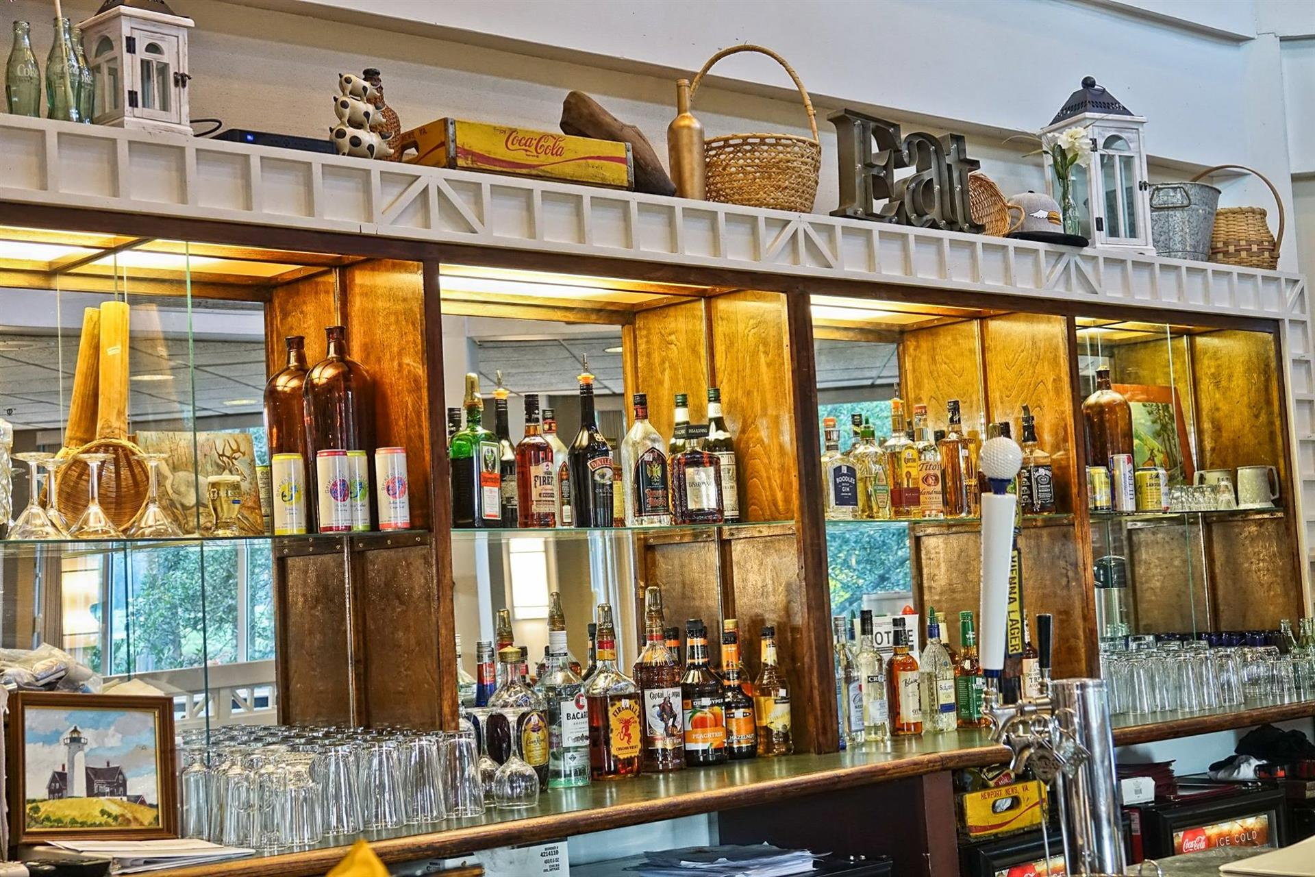 bar area setup with a wall display of various wine and liquor bottles behind the counter