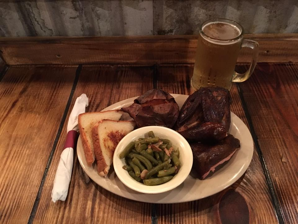 BBQ chicken on a plate with green beans, slices of toasted bread and a baked potato with a pint of beer