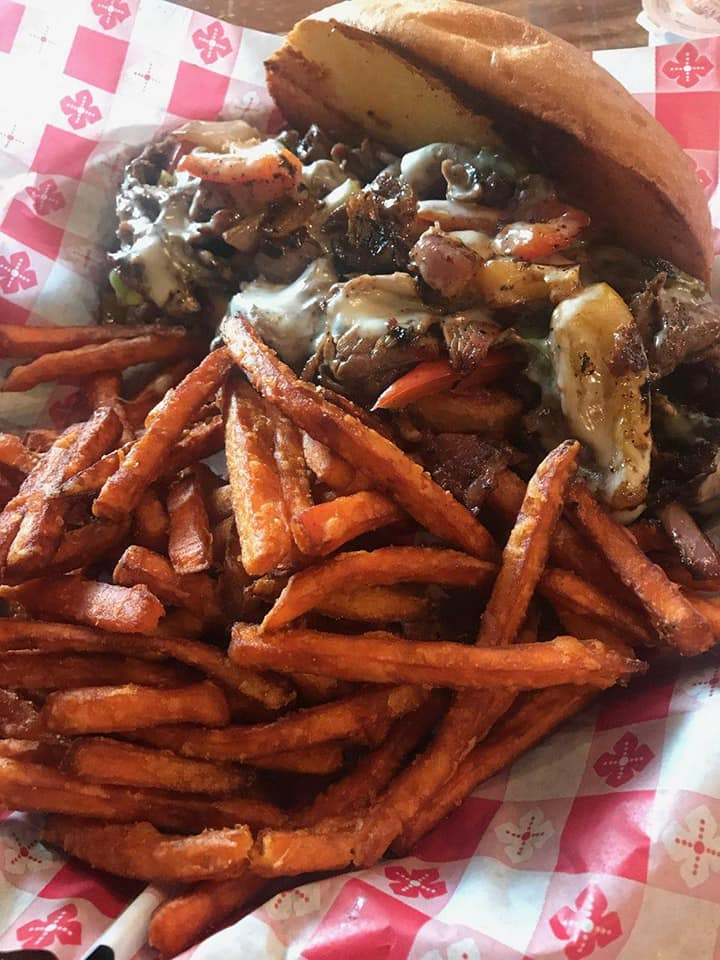 Grilled steak sandwich with cheese and sauteed peppers with sweet potato fries