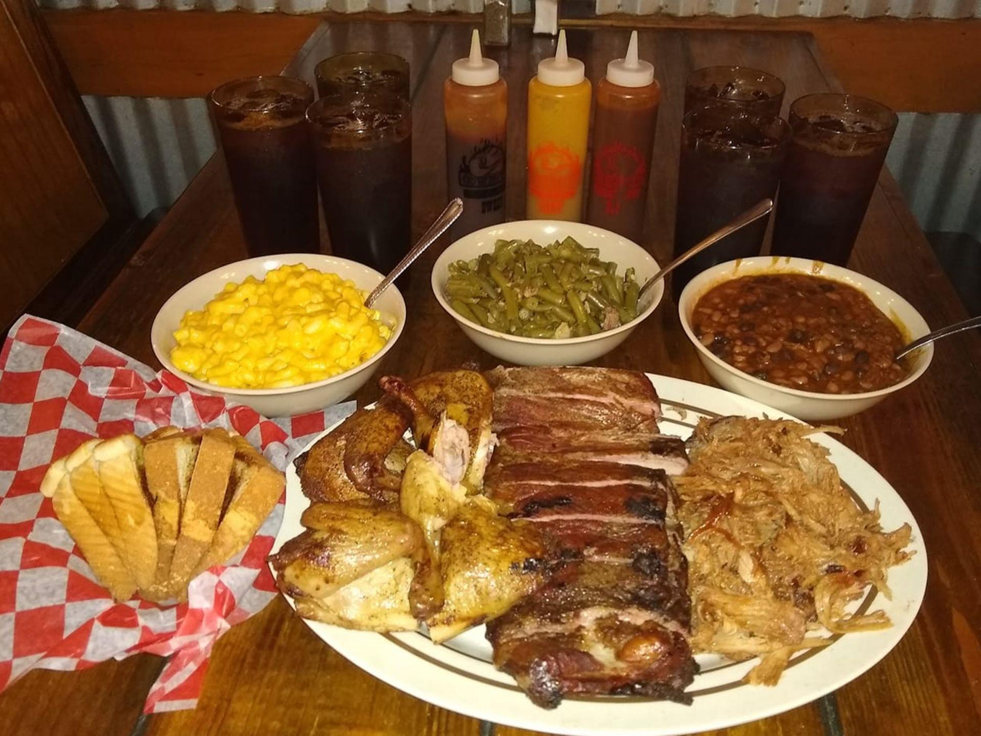 Rack of BBQ ribs on a plate with BBQ chicken and pulled pork, toasted bread, mac and cheese, green beans, baked beans and an assortment of sauces in bottles