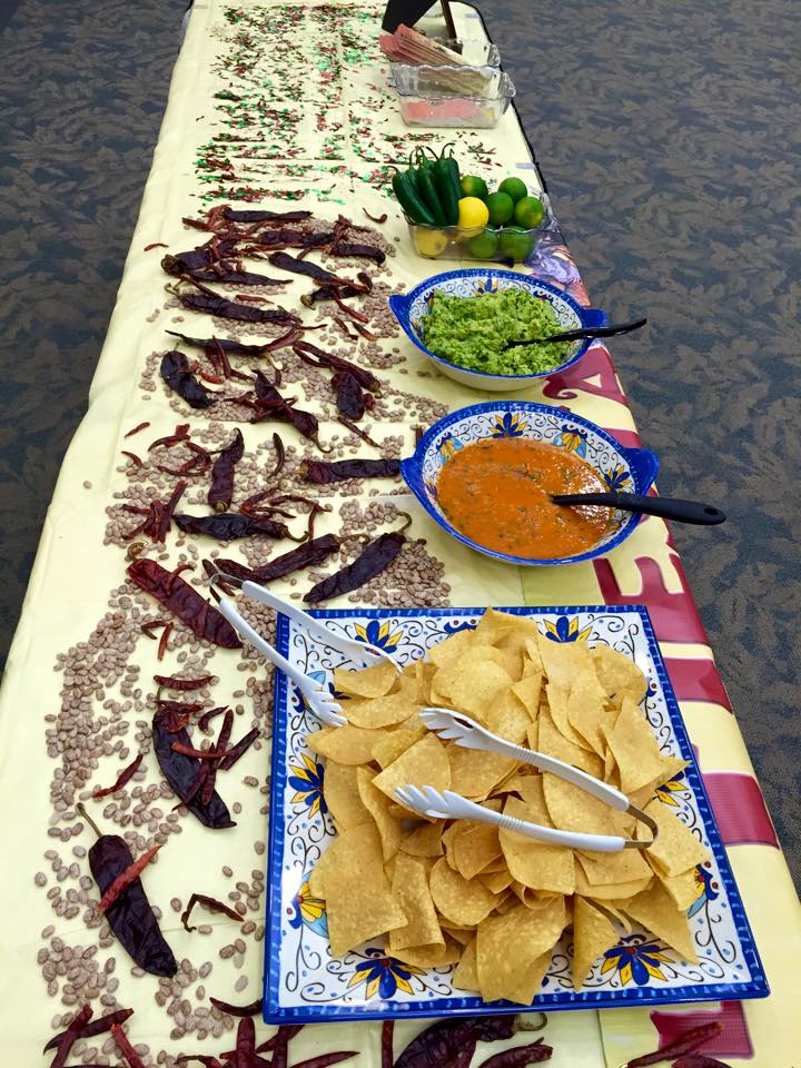 Table set up with a tray tortilla chips and bowls of salsa and guacamole