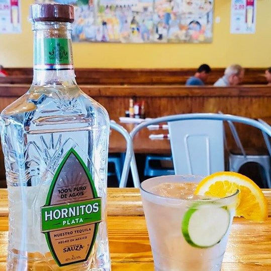 Bottle of Hornitos tequila next to a tequila cocktail with a lime and orange slice