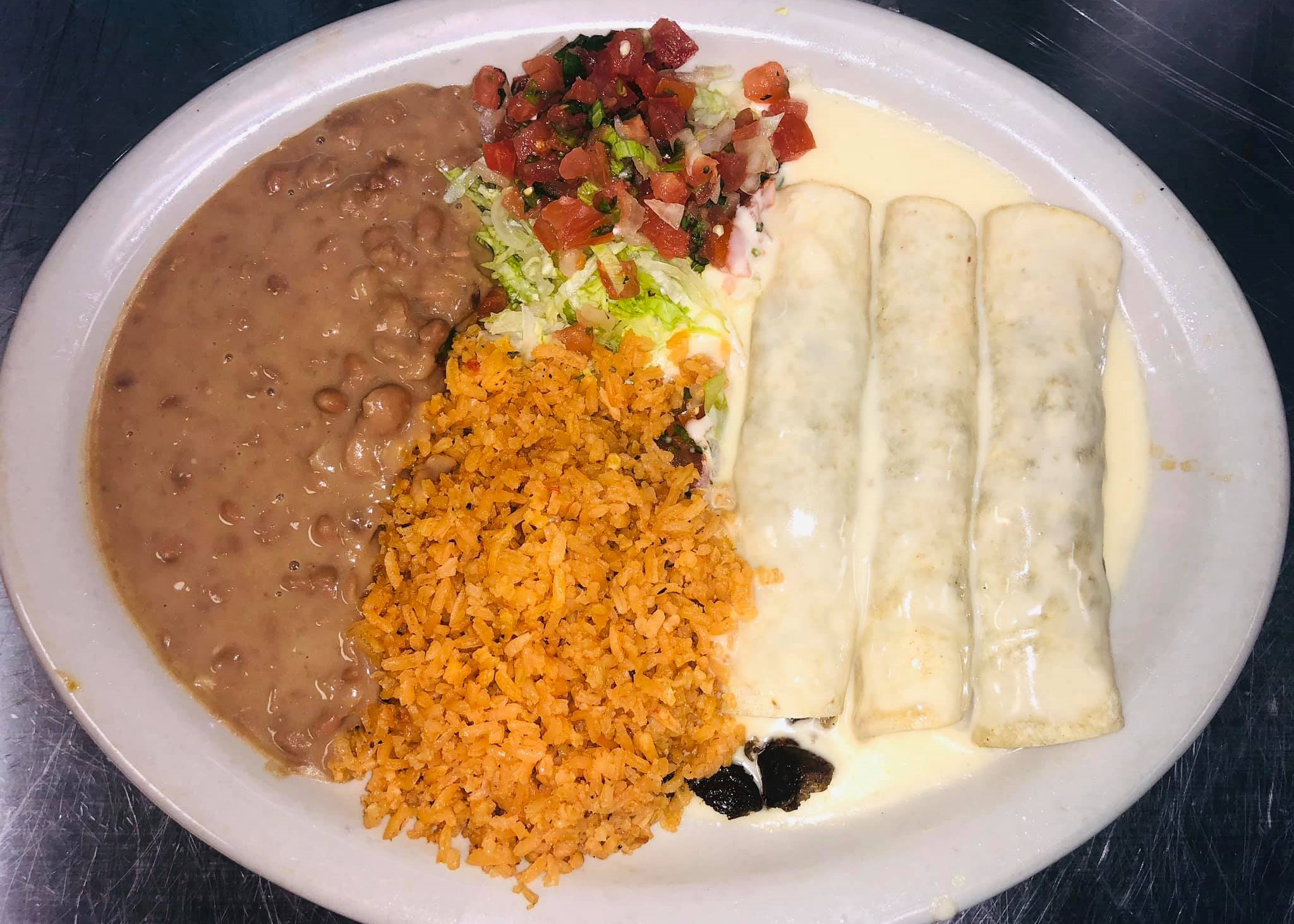 Enchiladas in cheese sauce with rice and beans