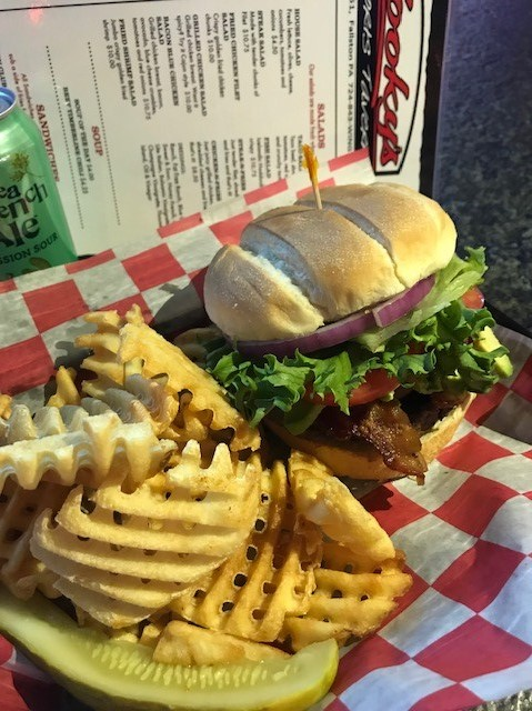 burger with bacon, tomatoes, lettuce with a side of fries