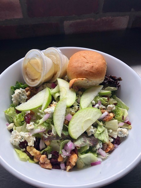 salad with vegetables, apple slices and a roll on top