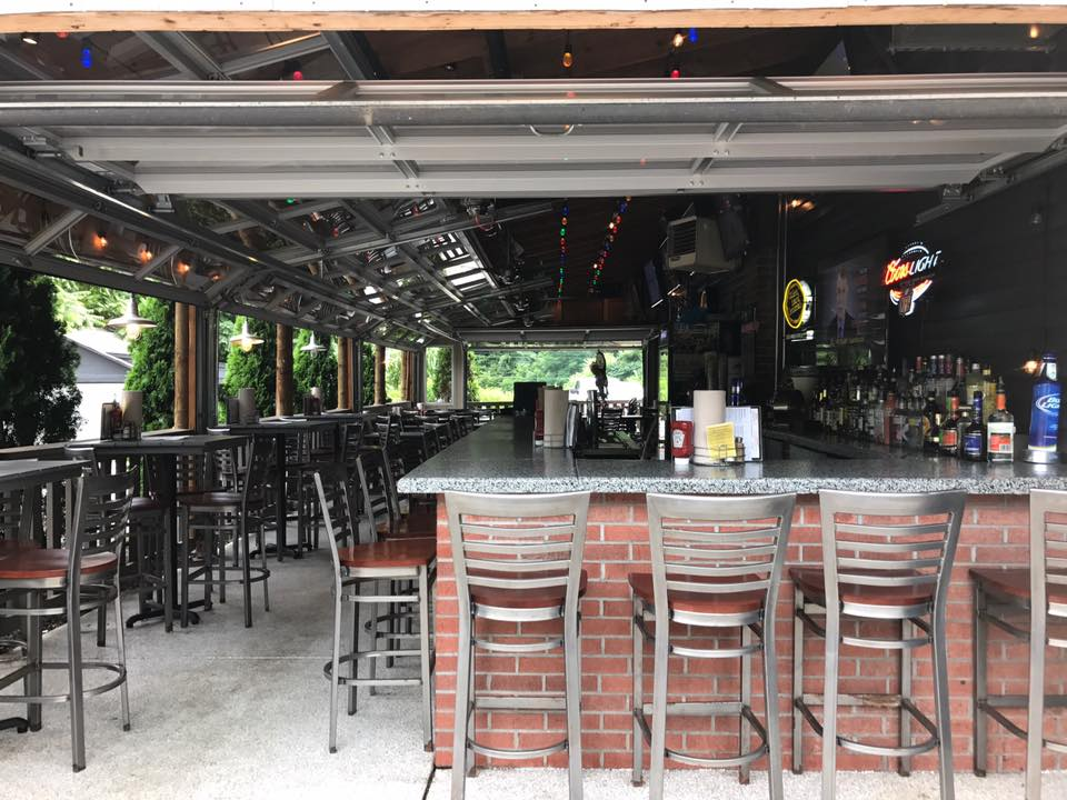 exterior bar patio with chairs, stools and large bar