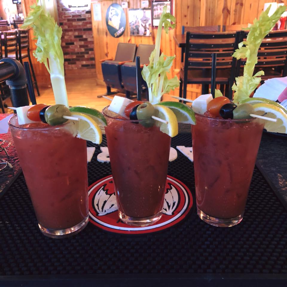 three bloody marys on a counter with olives