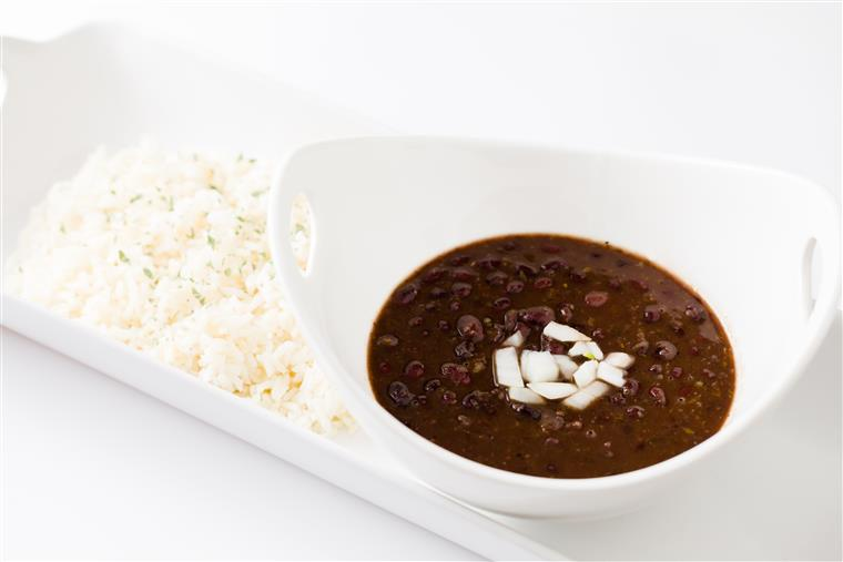 black bean soup with chopped onions and a side of white rice