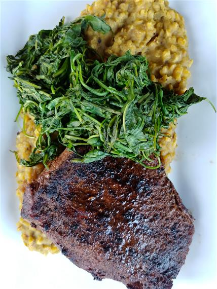 Grilled steak topped with sautéed spinach, over creamed corn