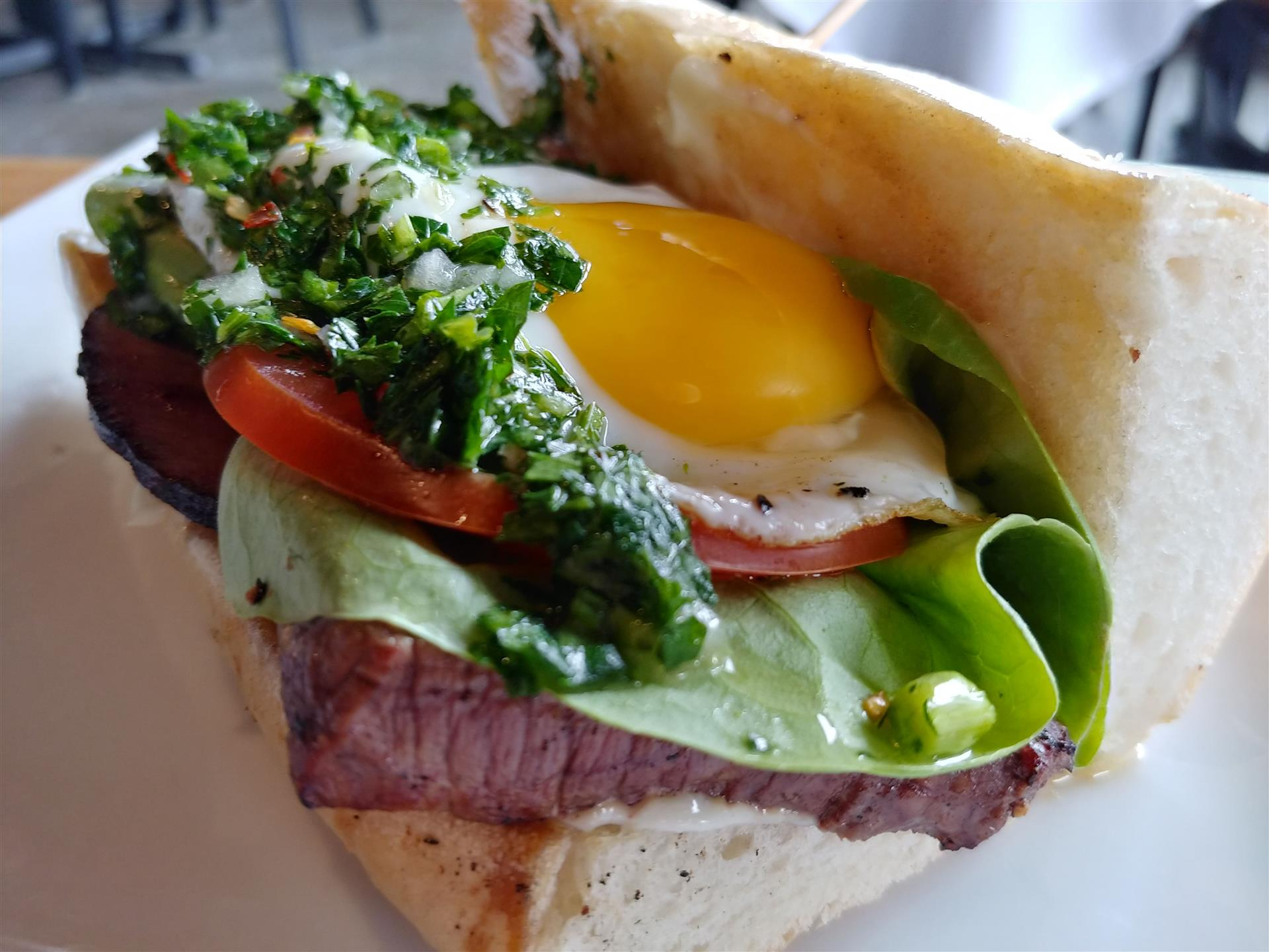 Steak sandwich topped wit lettuce, tomato, and a sunny side up egg