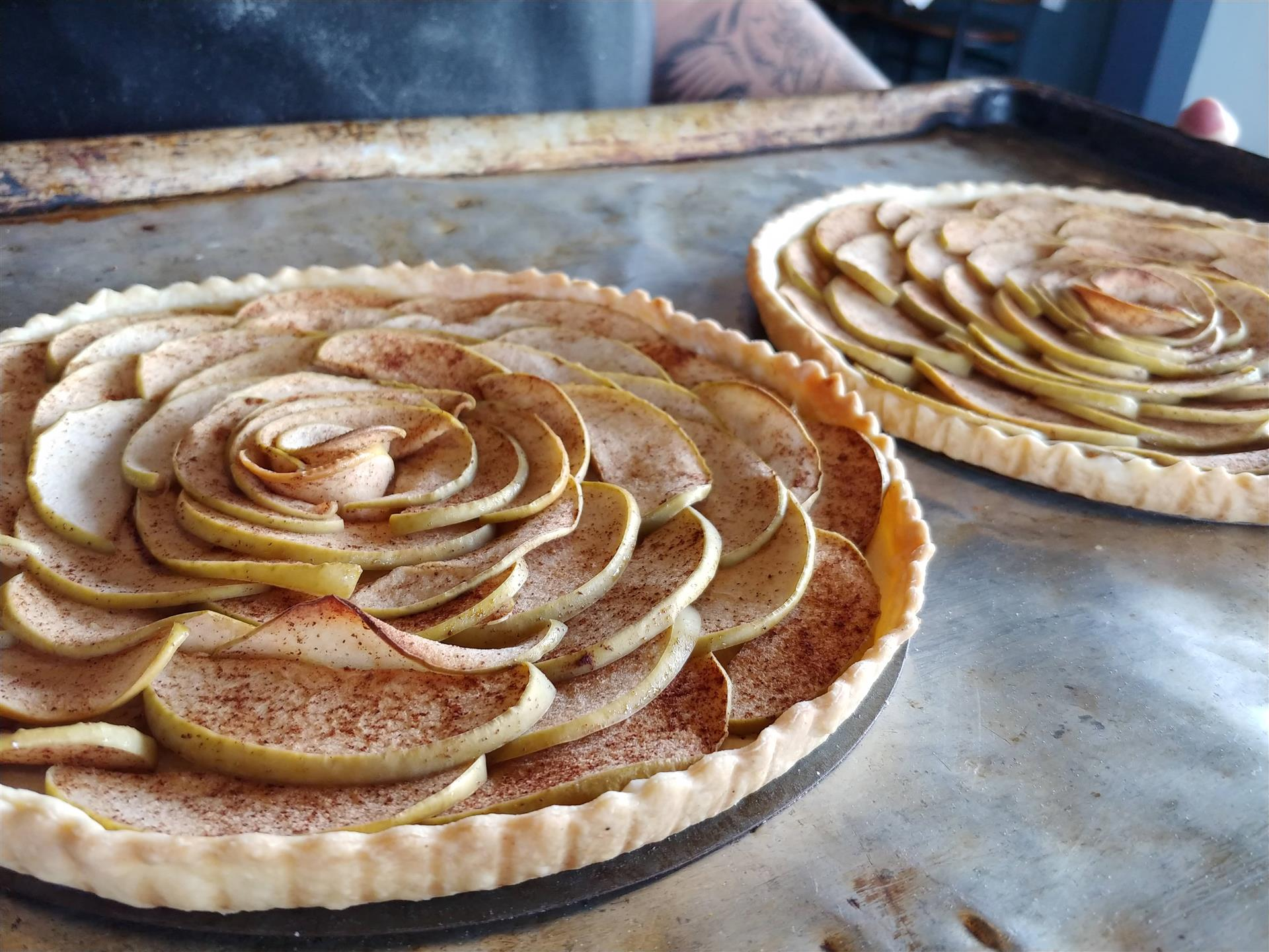 a full apple pie topped with apples to mimic flower pedals