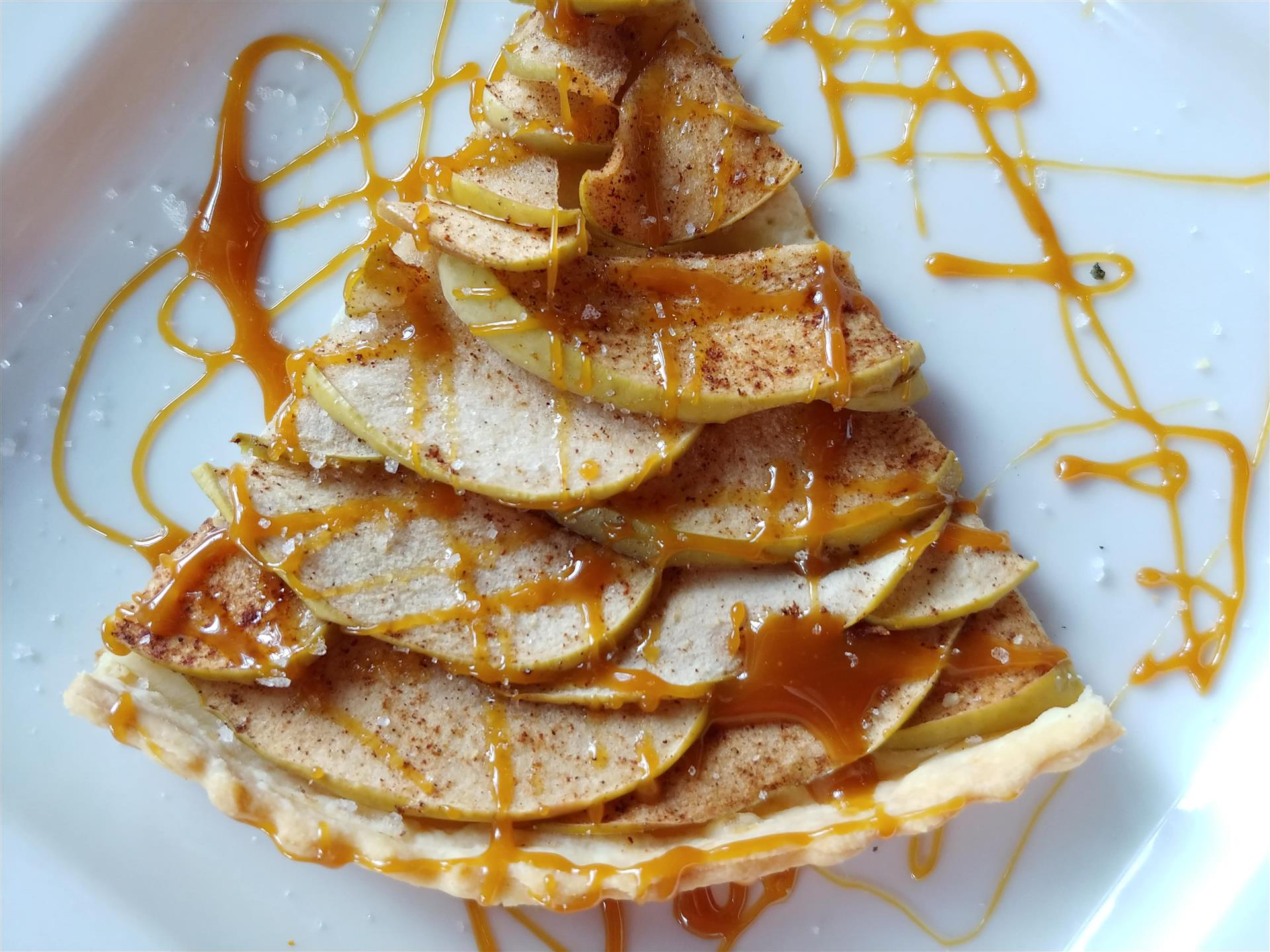 A slice of apple pie topped with cooked apples and a caramel drizzle