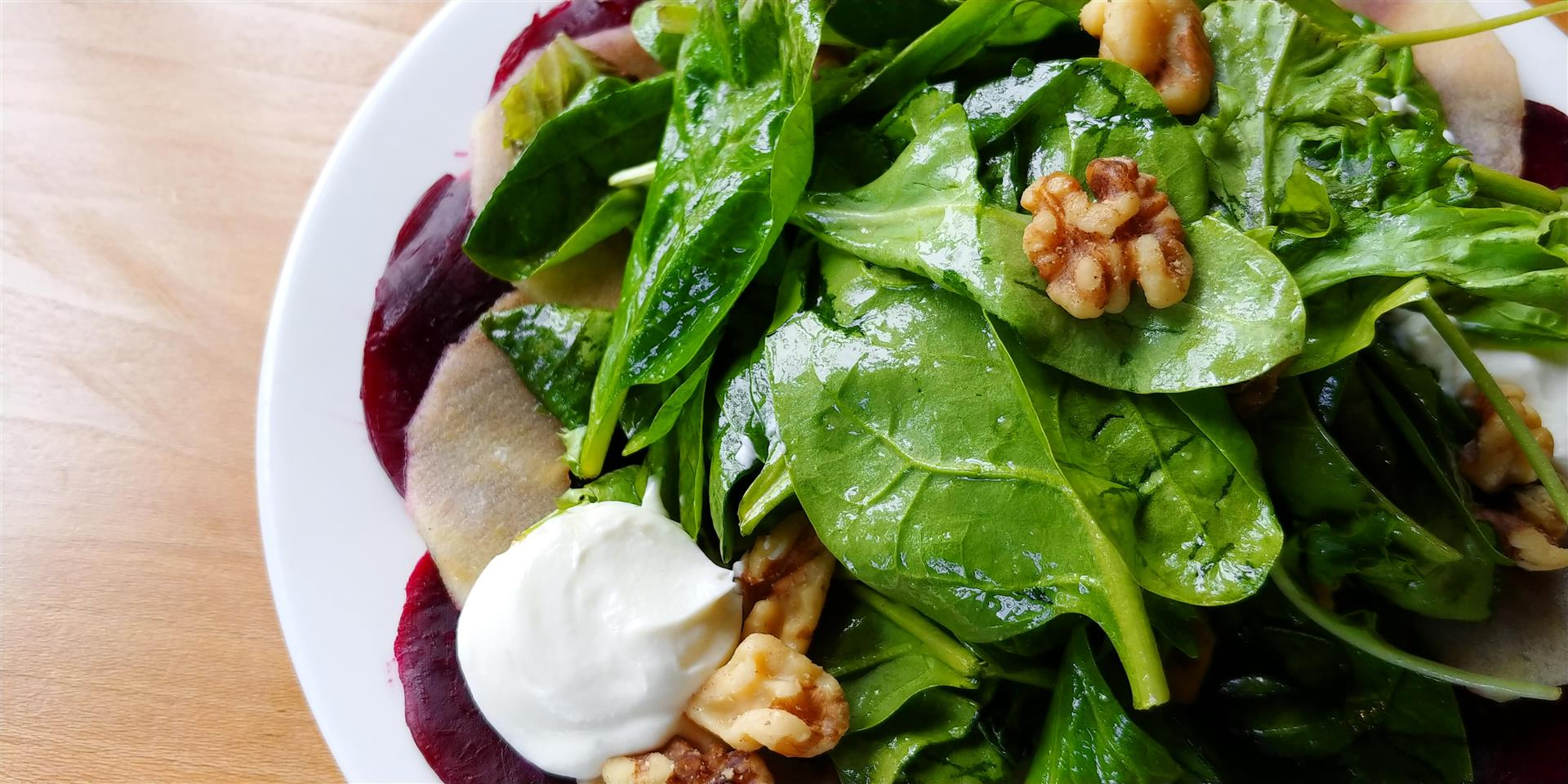 a spinach salad with beats and walnuts on a plate
