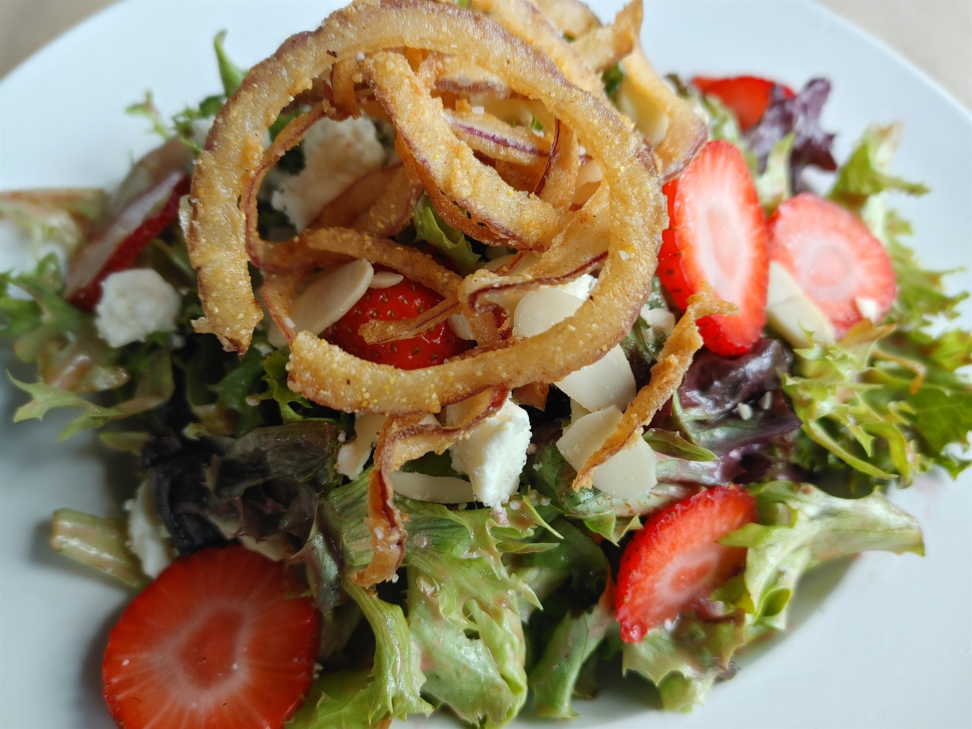 strawberry salad. mixed greens, fresh strawberries, almonds, and feta tossed in a strawberry vinaigrette and topped with crispy onions