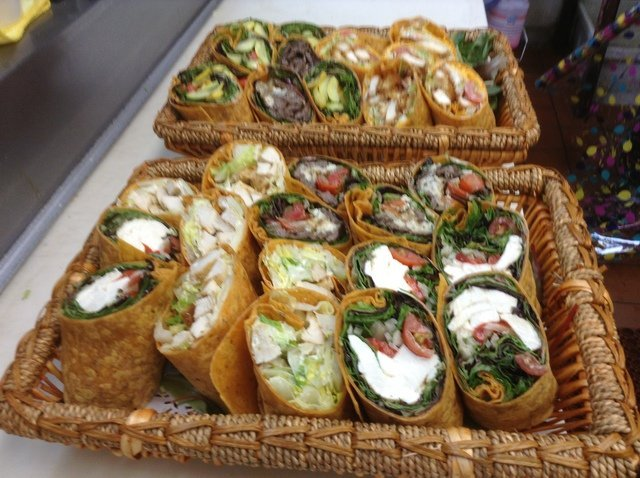 An assortment of wraps cut in half in a wood basket