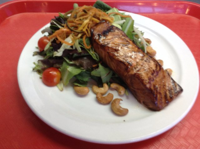 Grilled salmon filet over a mixed green salad with cashews