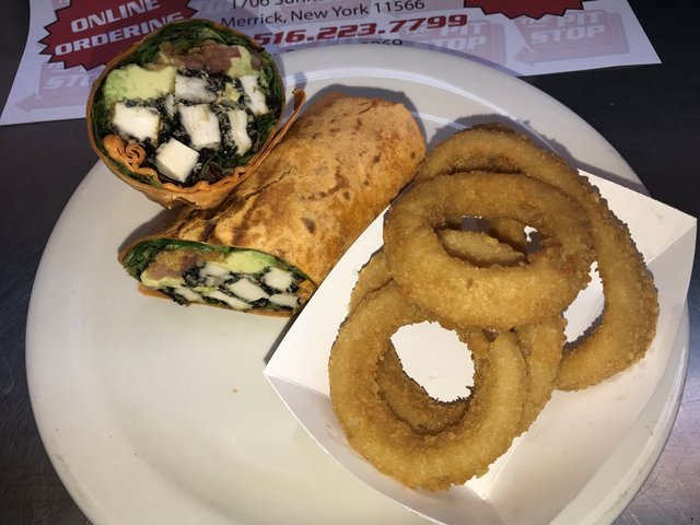 Grilled chicken and avocado wrap with a side of onion rings