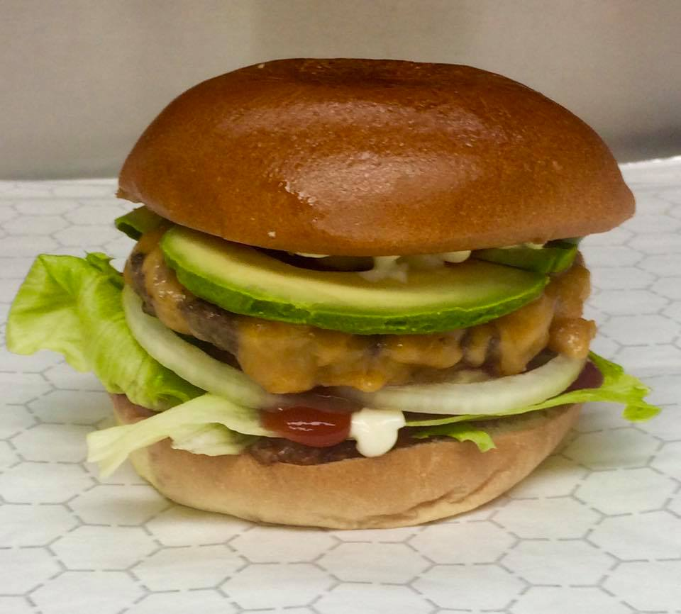 Cheese burger on a bun with avocado, onion, ketchup and lettuce