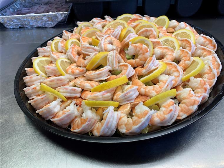 Shrimp cocktail platter with sliced lemon.
