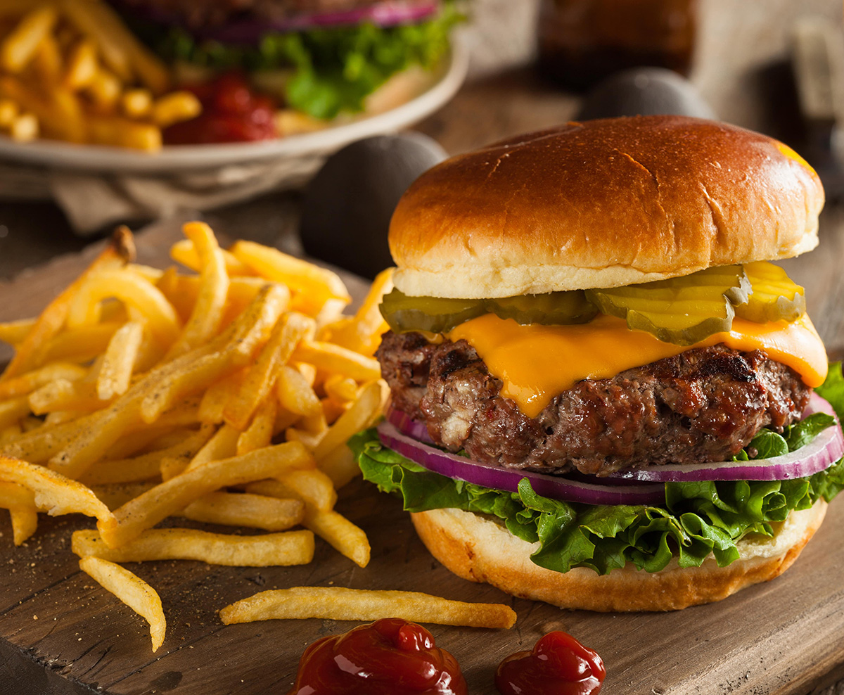 Burger with fries on a cutting board