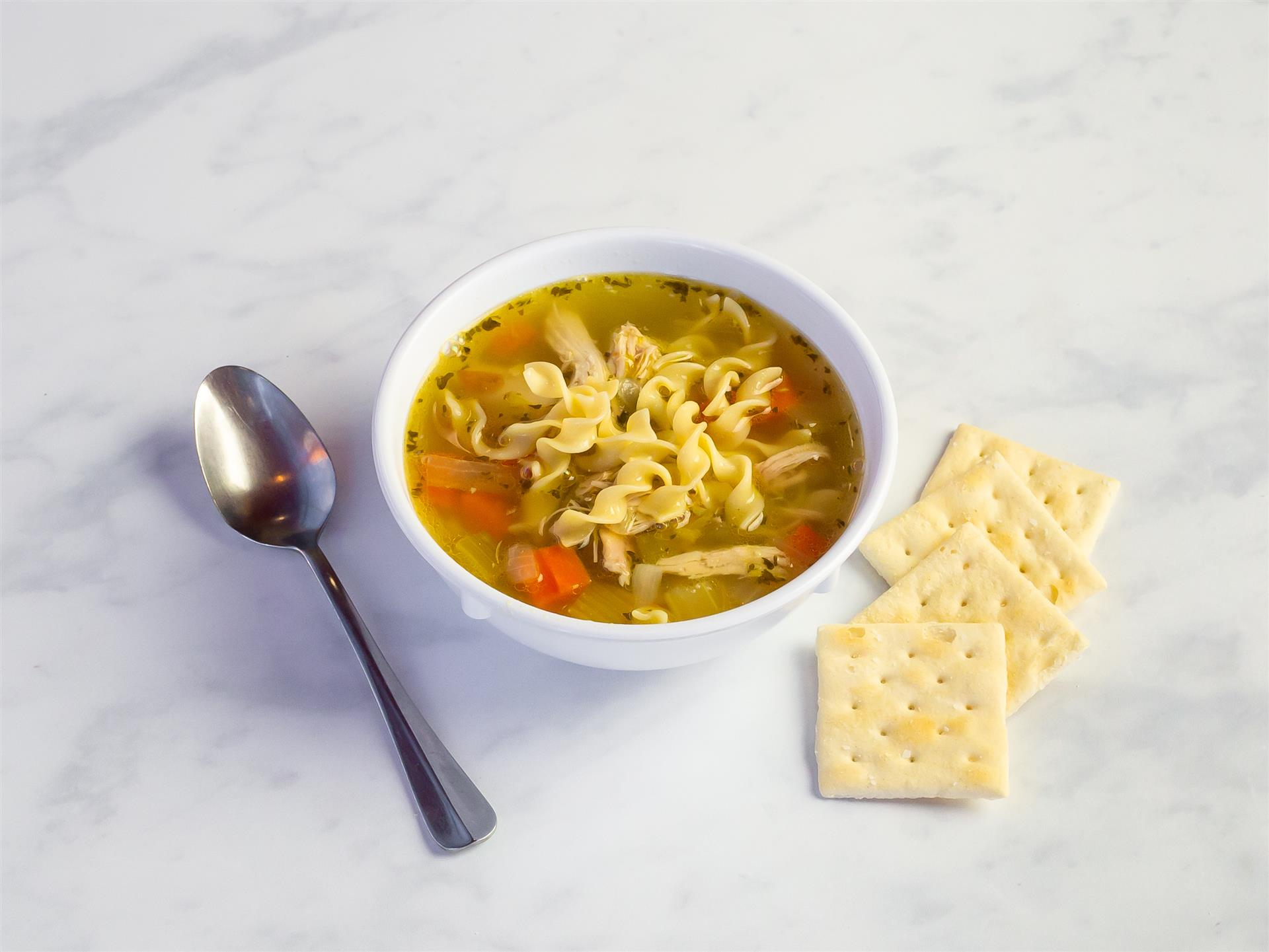 chicken noodle soup in a bowl with crackers