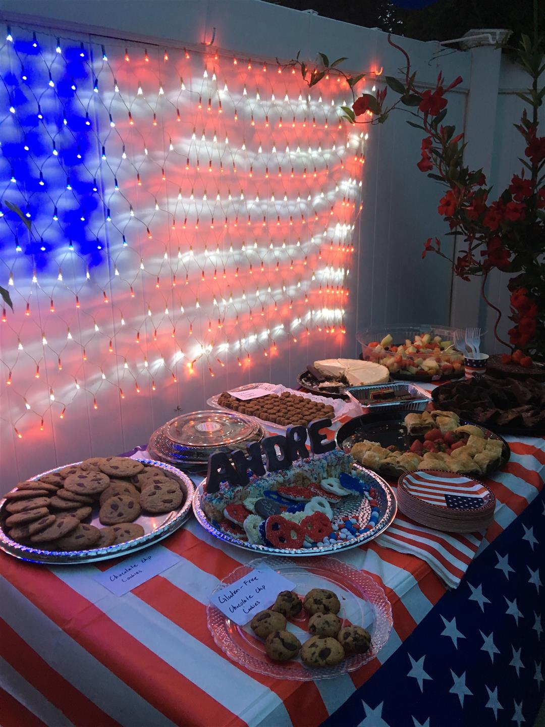 table of assorted cookies and desserts, with american flag in lights behind table
