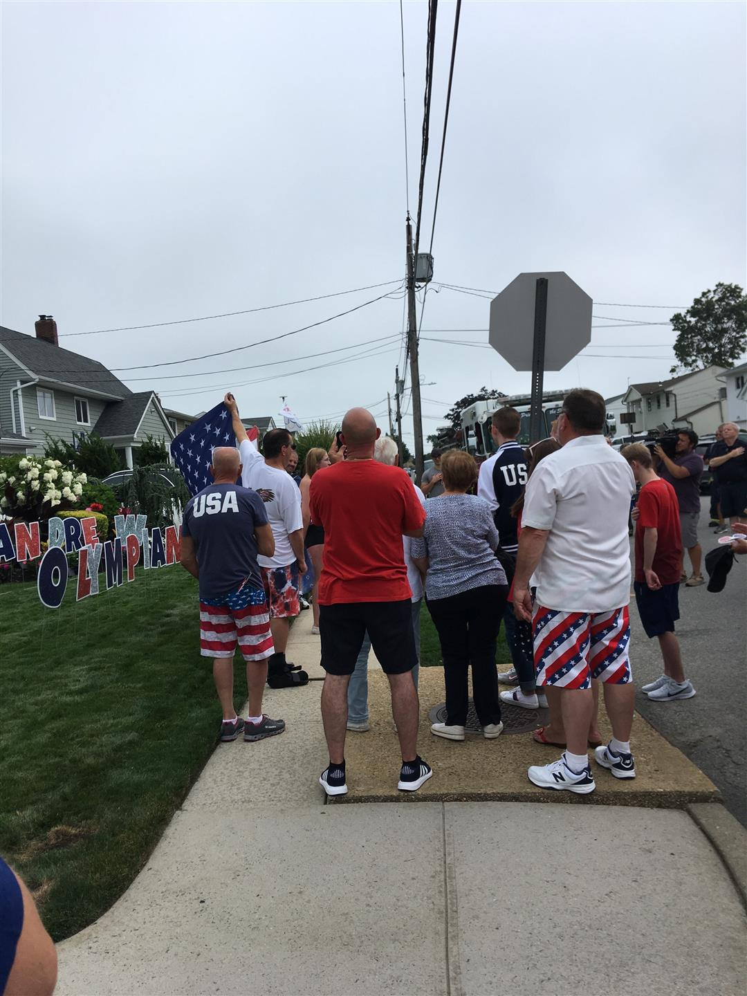 people gathered on a sidewalk to celebrate USA silver medalist in diving Andrew Capobianco