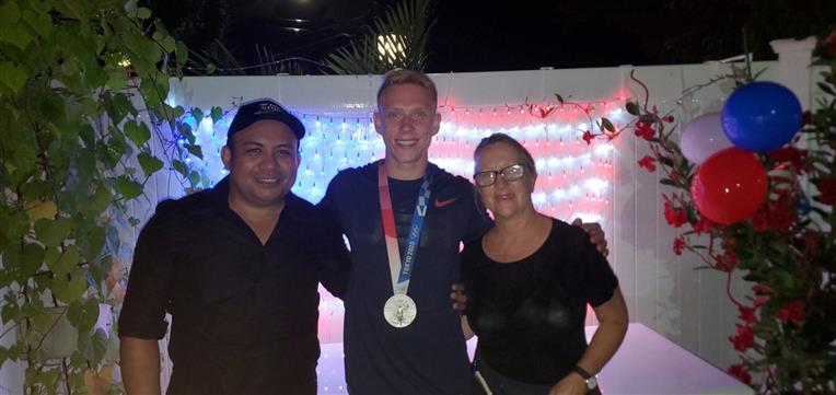 owners standing with Andrew Capobianco - USA silver medalist in diving