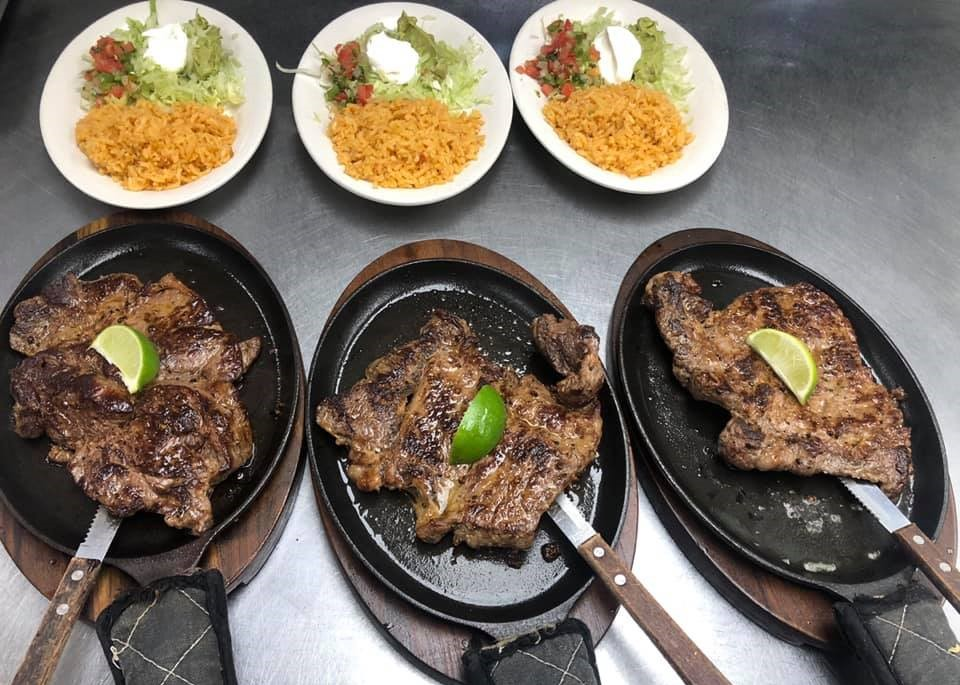 Steak fajitas on a skillet with a lime and a knife next to plates of rice, sour cream, lettuce and salsa
