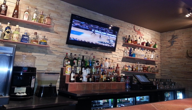 Full bar with liquor bottles on shelves behind bar and TV mounted to wall.