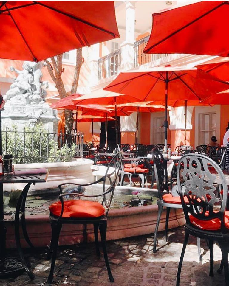 outdoor patio area with tables, chairs and umbrellas