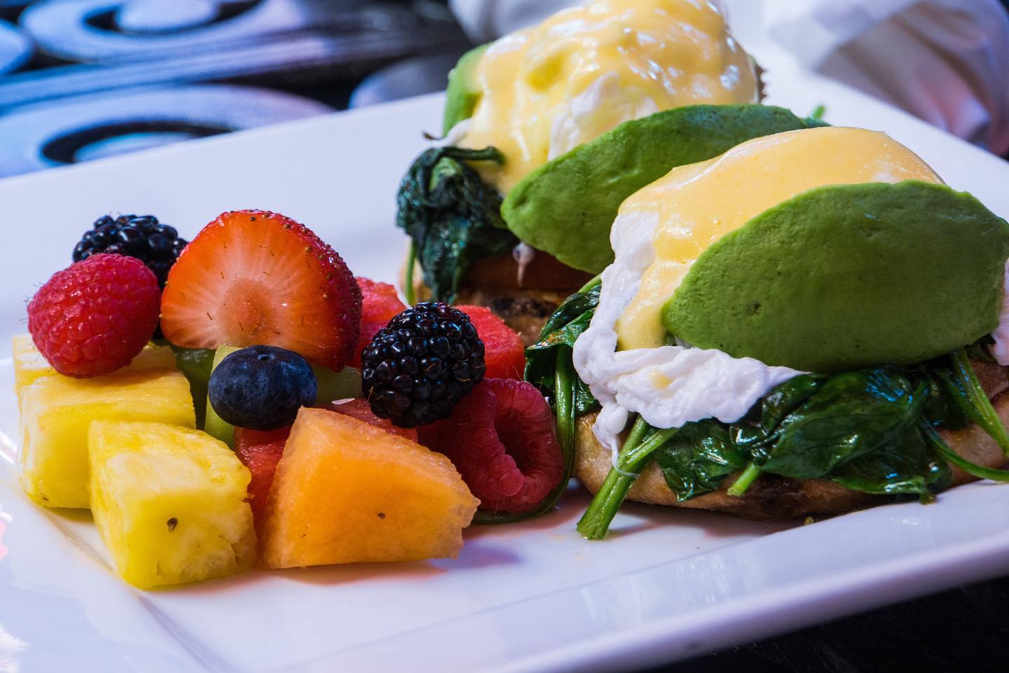 eggs benedict sandwich with a side of fresh fruit