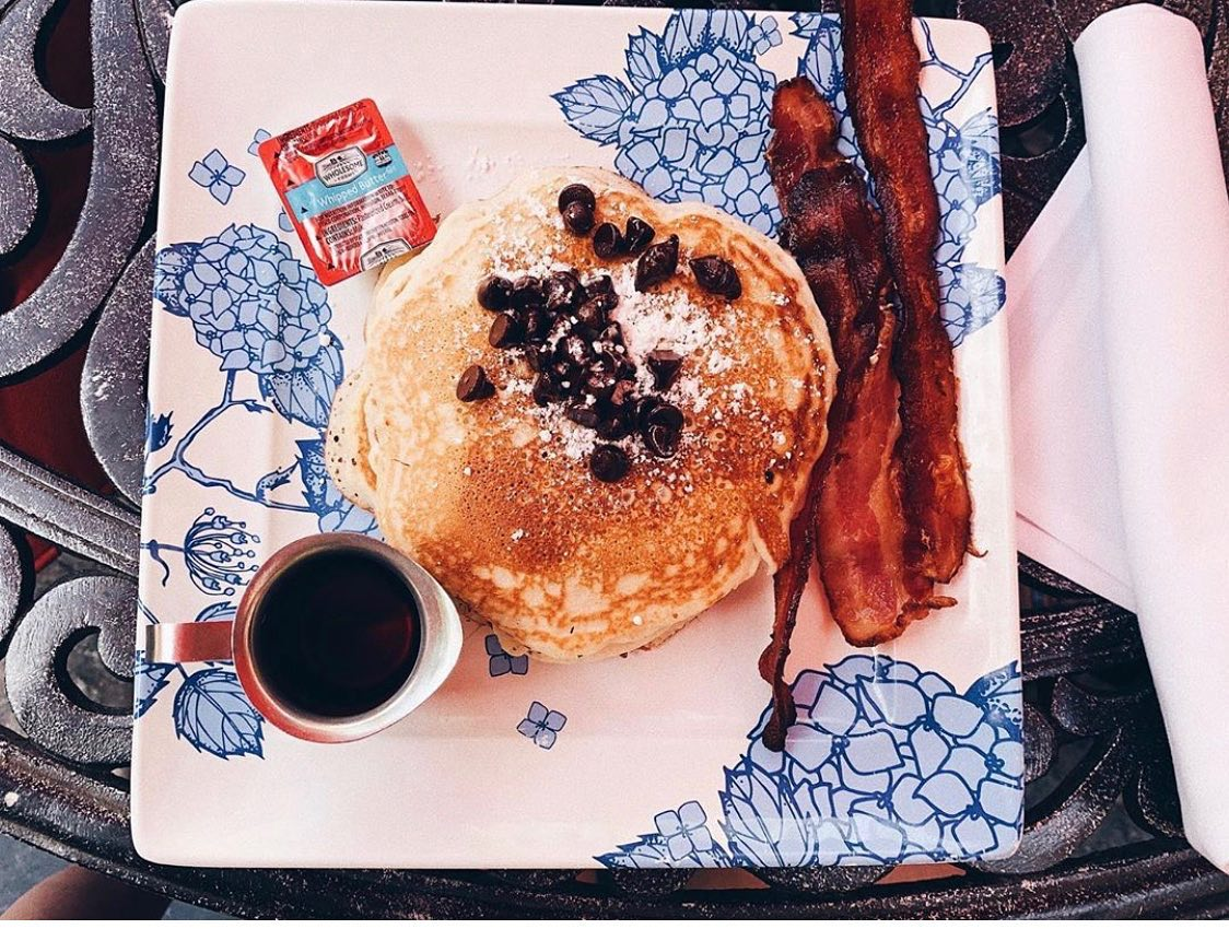 pancakes with bacon and a side of syrup on a plate