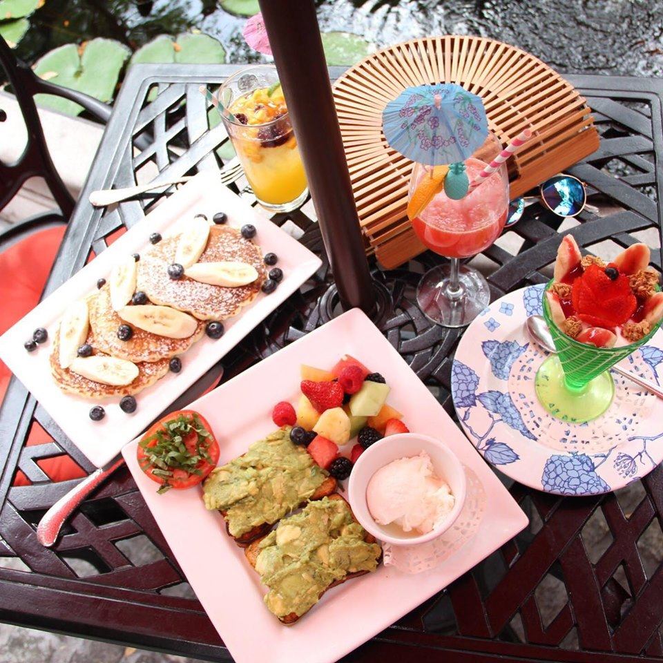 various entrees being displayed on an outdoor table with an umbrella