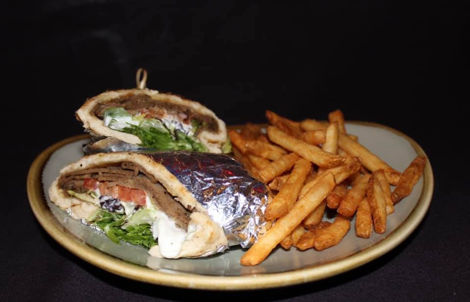 Gyro sandwich with lettuce and tomato on a plate with French fries