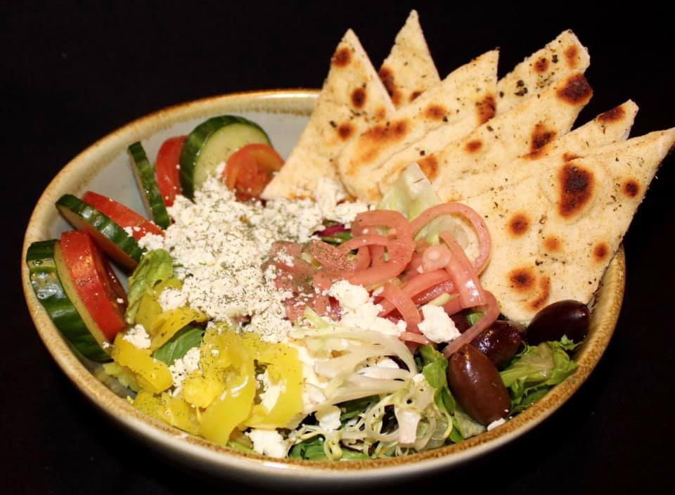 Greek salad with cucumbers and tomatoes, feta cheese, sliced banana peppers, onions and olives with pita bread slices